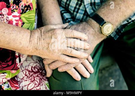 Manos con las arrugas de la pareja de ancianos, tomados de las manos de los ancianos juntos cerca, concepto de las relaciones, el matrimonio y las personas de edad, la amistad, el amor del hombre y de la mujer