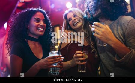 Las mujeres jóvenes felices fiestas amigos en el bar. Grupo de amigos para pasar un buen rato en la discoteca.