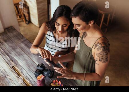 Las mujeres bloggers fotografías de cuenco de fruta y batidos jar colocado junto con una cámara DSLR para un artículo de blog de alimentos. Los bloggers de alimentos busca en th