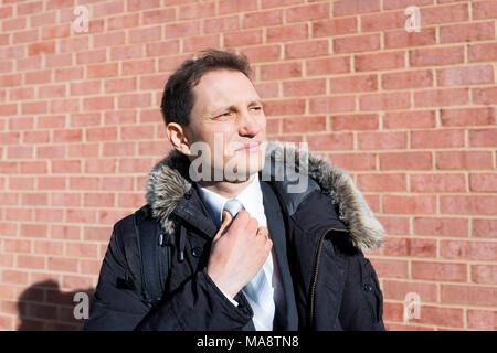 Guapo, atractivo joven empresario serio stern infeliz cara closeup retrato de pie delante de la pared de ladrillo, brida de fijación, en traje y corbata en int