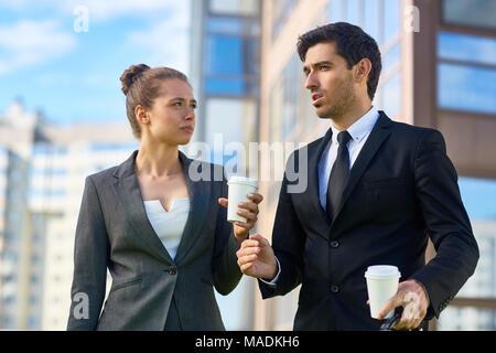 Joven agente de seguros en traje explicando su colega cómo hacer el siguiente paso en su negocio durante la piscina coffee-break