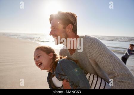 El padre con la hija de divertirse en invierno junto en la playa