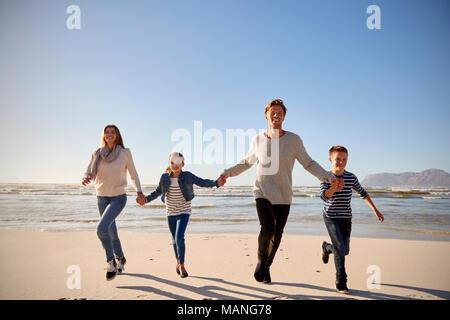 En invierno, la familia Playa tomados de la mano y corriendo hacia la cámara