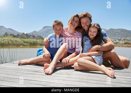 Retrato de familia sonriente sentado en el embarcadero de madera por el lago