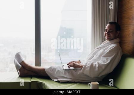 Sonriente joven empresario trabajando en equipo portátil vestidas de blanco albornoz sentado cerca de la ventana con una taza de café mirando al amanecer con vistas a la ciudad. Concepto de motivación