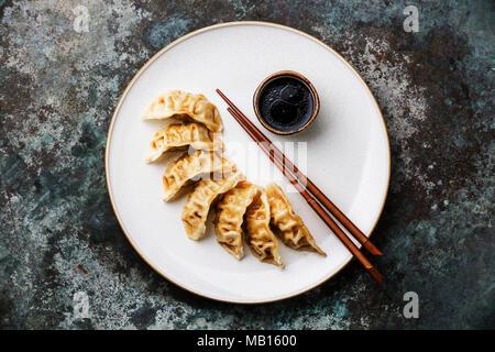 Los dumplings Gyoza en la placa, los palillos y la salsa de soya sobre fondo de metal