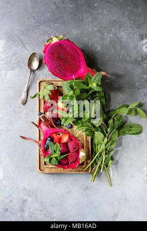 Vegan ensalada de frutas con fresas y menta en rosa dragon fruit con ingredientes por encima en madera sirviendo junta azul sobre fondo de textura. Principio V