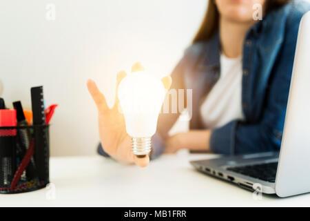 La mujer de negocios, la mano que sostiene el diseñador de bombilla, el concepto de nuevas ideas con la innovación y la creatividad.