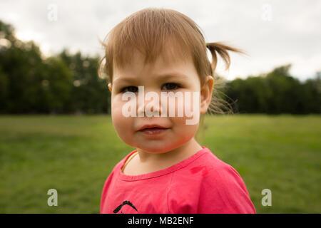 Cute Little Girl in niño vestido rosado jugando en el parque enfrente de la pasto verde
