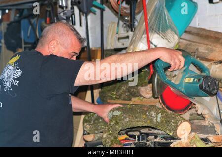 Un varón de mediana edad cortando un registro utilizando una sierra tronzadora / chop en un desordenado garaje y no usaban ningún equipo de seguridad