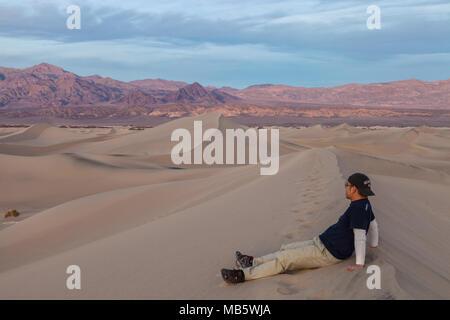 Un excursionista se sentó sobre la duna de arena y contemplar el vasto paisaje en Mesquite Flat dunas de arena en el Parque Nacional Valle de la Muerte, California, Estados Unidos.