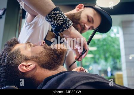 Joven barbudo listo para afeitarse en la peluquería de un hábil peluquero