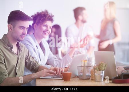 Un empresario trabajando en su computadora portátil y su mujer sonriendo y hablando junto a él