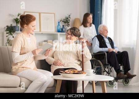 Enfermera de leer un libro a una mujer mayor con otro pensionista sentado en una silla de ruedas en el fondo Foto de stock