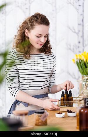 Vendedora organizando los aceites naturales en la tienda con cremas orgánicos Foto de stock