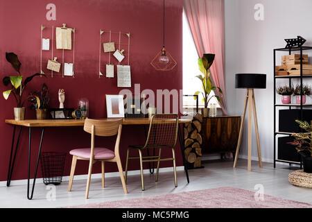 Lámpara de madera y plantas en rojo oscuro interior home office con silla y escritorio con poster