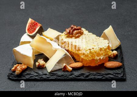 Camembert queso con miel, higos, nueces de losa de piedra Foto de stock