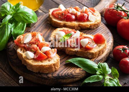 Bruschetta con tomate, albahaca y queso mozzarella sobre la plancha de madera. Italiano tradicional aperitivo o snack, antipasti Foto de stock