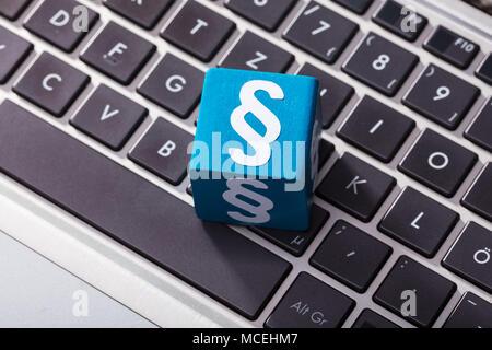 Vista aérea del símbolo de párrafo sobre el bloque de madera del azul en el teclado portátil