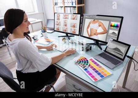 Feliz joven diseñador que trabaja con fotografías en varios equipos en el lugar de trabajo