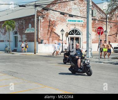 Una escena callejera en Key West, Florida, con la compañía de Ron Hemingway en el fondo.