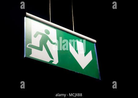 Salida de emergencia cartel colgado en una pared. Señal de salida de emergencia en un edificio iluminado en color verde