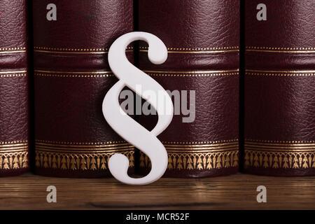 Close-up de color blanco Símbolo de párrafo inclinado sobre libros de derecho en sala