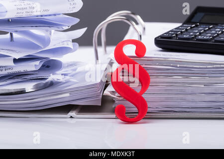 Close-up de color rojo Símbolo de párrafo apoyándose en documentos