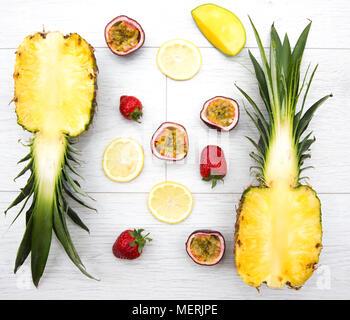 Mirando de arriba abajo a la fruta fresca como la fruta de la pasión, mango, fresa y piña, que son los ingredientes para un batido tropical. Foto de stock