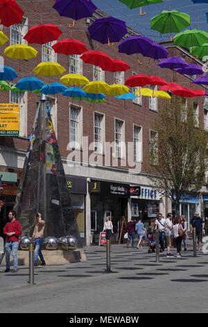 La Exeter Enigma y coloridas sombrillas de primavera. Exeter High Street, Devon, Reino Unido. Abril, 2018.