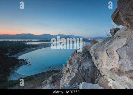 Vista superior de la bahía con playas de arena y las luces de una aldea al atardecer Porto Giunco Villasimius Cerdeña Cagliari Italia Europa