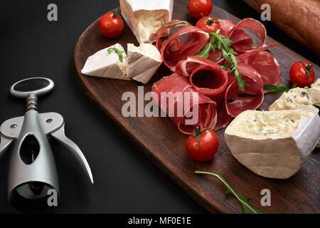 Queso, jamón, pan, verduras y especias en placa de madera sobre fondo negro con espacio de copia Foto de stock