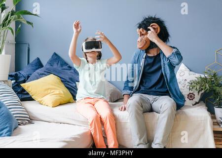 Padre portando máscara mono Mira hijo llevaba gafas VR en casa