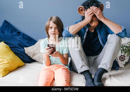 Padre portando máscara mono sentado junto al hijo en casa utilizando el smartphone