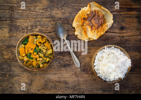 Plato de curry con coliflor, calabacita calabaza, espinaca y cilantro, papadam y arroz Foto de stock