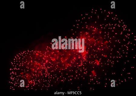 Fuegos artificiales y humo en color rojo contra un cielo negro como fondo.