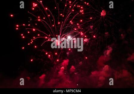 Fireworks con senderos y humo en color rojo contra un cielo negro como fondo.