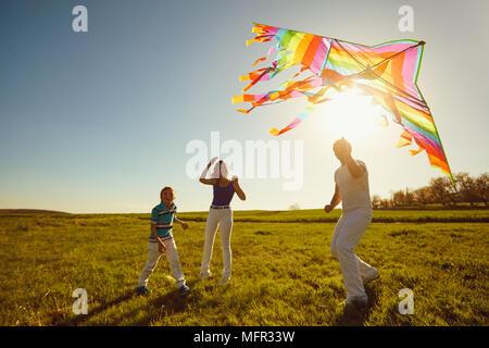 Familia feliz jugando con una cometa en la naturaleza en primavera, verano.