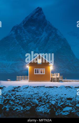 Amarillo tradicional Olstinden Rorbu cabina con el pico de la montaña al atardecer en invierno, la aldea de Sakrisoy, archipiélago de las islas Lofoten, Noruega