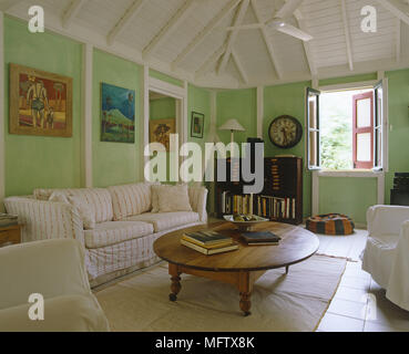 Sala de estar con piso de baldosas de madera en el techo y sillones con pinturas en la pared Foto de stock