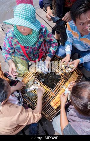 Los comerciantes musulmanes Cham con una captura de cangrejos en el mercado de cangrejo en Kep, Camboya