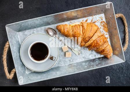 Desayuno ligero desde croissants frescos y una taza de café en la bandeja gris