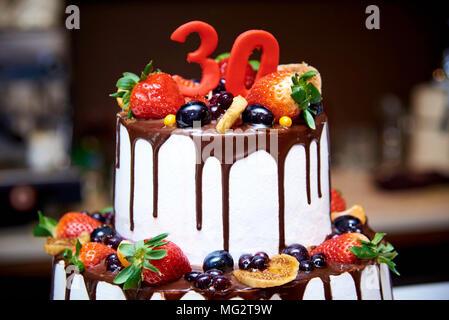 Pastel blanco de dos niveles con frutas y chocolate decorada con una figura de treinta close-ups.
