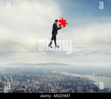 El empresario lleva una pieza del puzzle mientras él caminando sobre una cuerda. concepto de pieza faltante