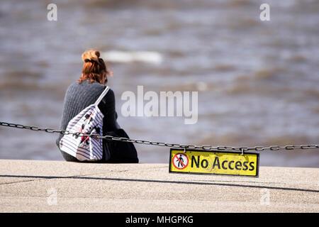 Una solitaria mujer sentada solitaria mirando la marea vienen en el paseo marítimo de Blackpool, detrás de una cadena de seguridad de acceso en Lancashire, Reino Unido.