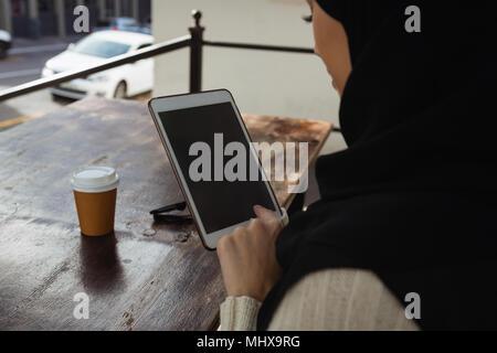 El Hijab mujer utilizando digital comprimido en cafe Foto de stock