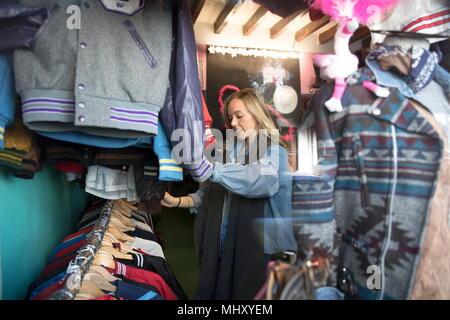 Mujer joven mostrando Vintage ropas en thrift store Foto de stock