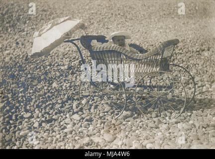 Antique c1900 fotografía, bebé en un cochecito de bebé victoriano en una playa. Ubicación desconocida, probablemente de Nueva Inglaterra en los Estados Unidos. Fuente: impresión fotográfica original.
