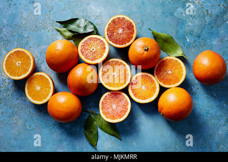 Sangre naranjas enteras y cortadas en una superficie azul (visto desde arriba). Foto de stock
