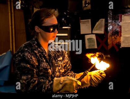 SANTA RITA, Guam (Dec. 8, 2017) Casco Técnico de Mantenimiento de 3ª clase AnnMarie Liles, asignado a la licitación submarino USS Frank Cable (como 40), enciende una antorcha en el tubo tienda a bordo del Submarino USS Emory S. tierras de licitación (39), 8 de diciembre, después de ser nombrado chaqueta azul del año. Liles es deber asignado temporalmente a Emory S. Frank Cable tierra, mientras se encuentra en Portland, Oregon para su dique seco programados de mantenimiento fase de disponibilidad. (Ee.Uu. Navy photo by Mass Communication Specialist 2ª clase Michael Allen McNair/liberado)
